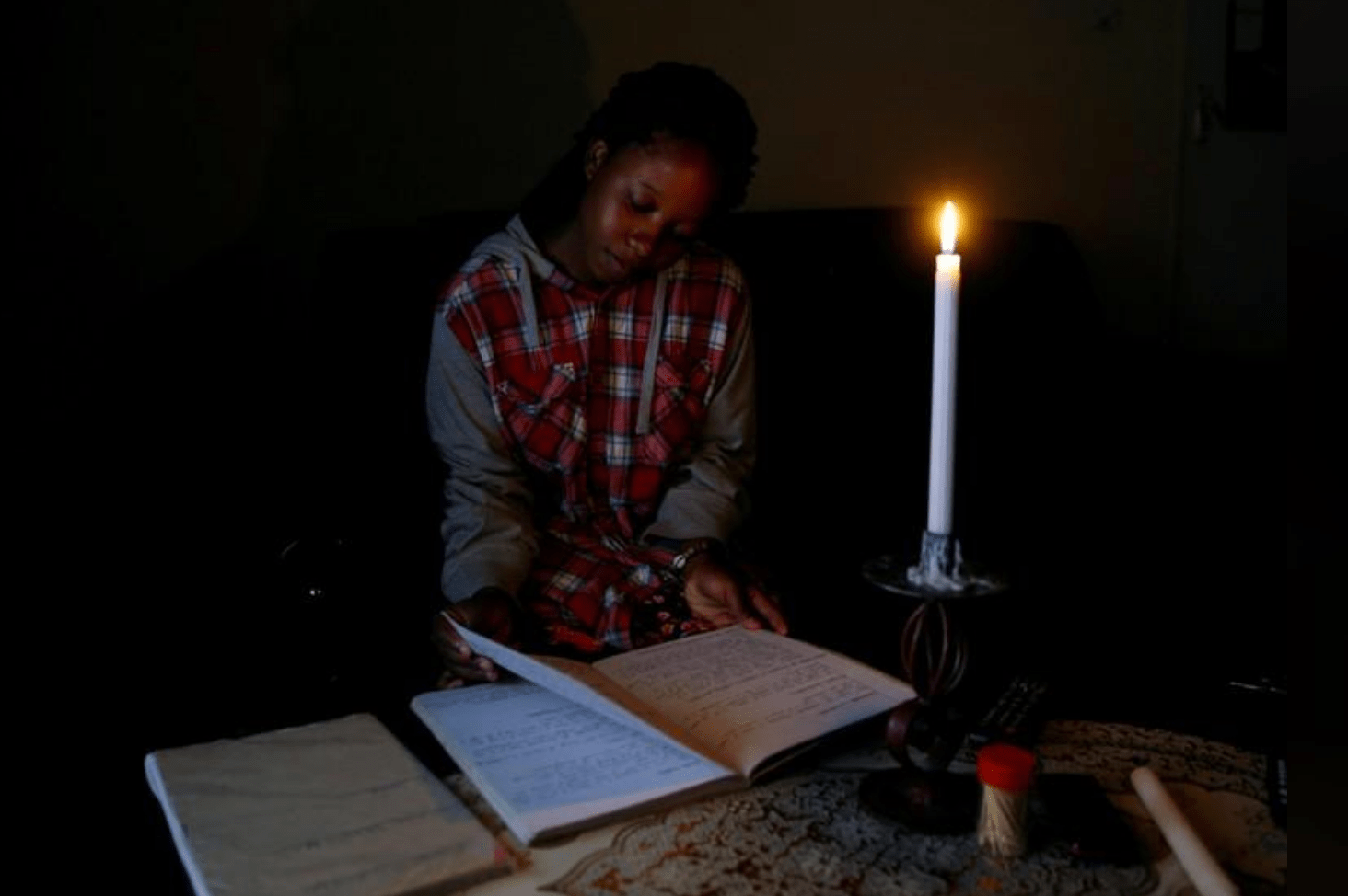 Student Rutendo Madziva reads by candlelight during an electrical power cut in Marondera, Zimbabwe, May 14, 2019. REUTERS/Philimon Bulawayo