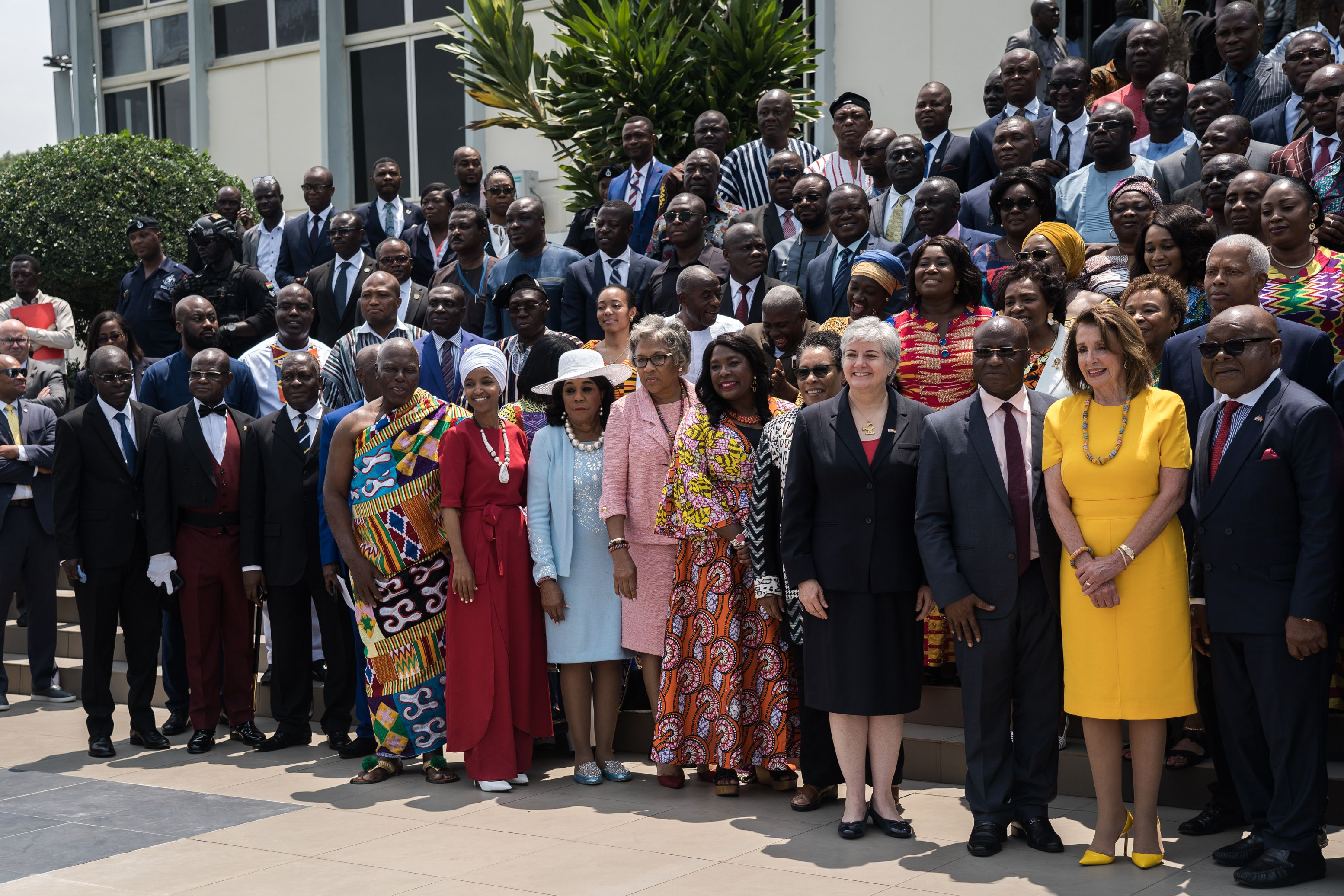 """US Speaker of the House Nancy Pelosi (2nd R), Speaker of Ghana's Parliament Mike Aaron Oquaye (R) and US Representative Ilhan Omar (5th L) pose for a family picture with members of Parliament in front of the Ghana's Parliament in Accra, on July 31, 2019 during a three-day visit to the country to mark the 400 years anniversary since the first slave shipment left the Ghana's coast for United States. - US House Speaker Nancy Pelosi condemned the """"grave evil"""" of slavery in a speech to Ghana's parliament marking 400 years since the first shipment of enslaved Africans to America. Pelosi was leading a delegation including members of the Congressional Black Caucus to the West African country, four centuries after the first slave ship arrived in Jamestown, Virginia from the continent. (Photo by Natalija GORMALOVA / AFP)        (Photo credit should read NATALIJA GORMALOVA/AFP/Getty Images)"""