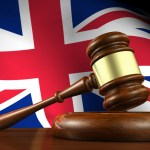 Uk law and justice concept with a 3d render of a gavel on a wooden desktop and the Union Jack flag on background.