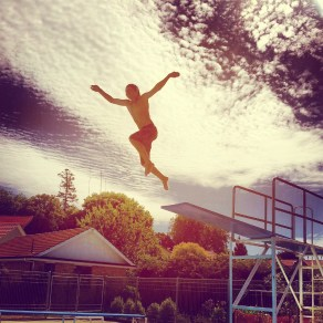 Boy jumping off high diving board at swimming pool