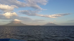 Two volcanoes in the distance across a large body of water.  the larger one to the left is cloud capped, the smaller to the right is free of cloud.