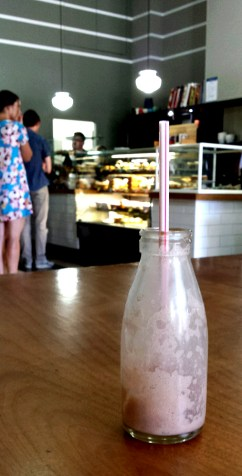 small milk bottle with straw sticking straight up on a table. This is in focus, in the background there is a cafe counter with people standing at it. It is blurred.