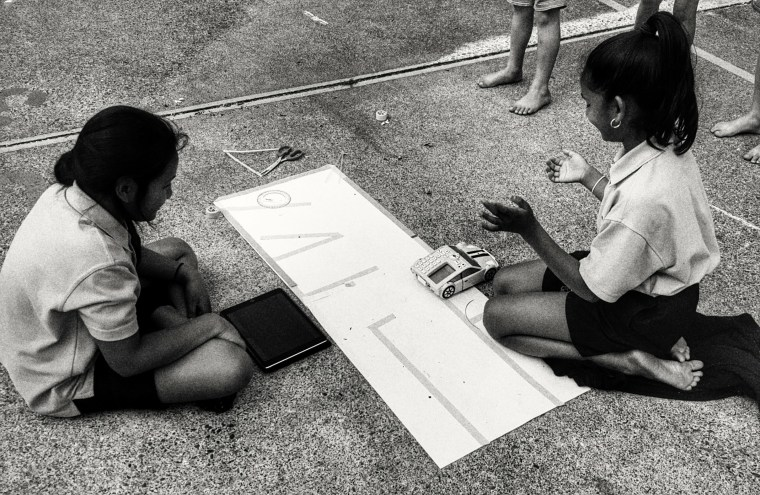 two girls working together. They are in a school playground, with a large paper map they have designed. They have a robotic car which they have programmed.