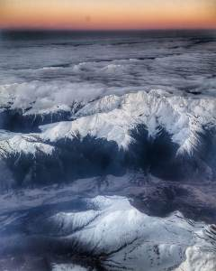 Mountains viewed from the air, covers with snow. Cloud in the valleys.