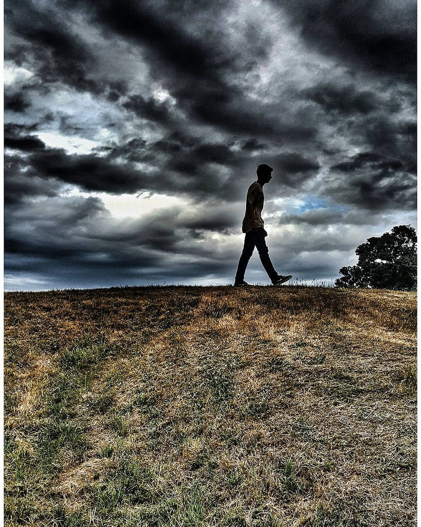 a young man walks across a field. Rain clouds scud across a dark sky.