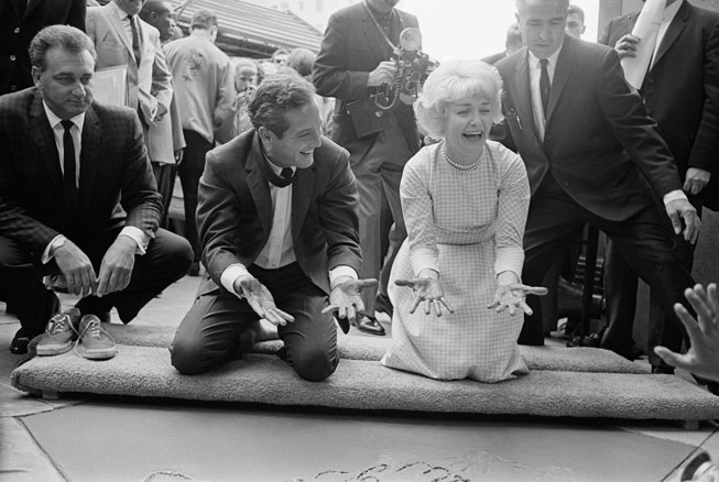 Newman and Woodward happily display cement-covered hands after leaving their prints in the forecourt of Grauman's Chinese Theatre, May 1963. From Bettmann/Corbis.