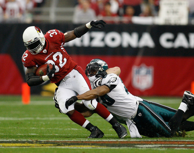 Edgerrin  James  of  the  Cardinals is  tackled  by  Eagles'  safety  Brian Dawkins  ................................
