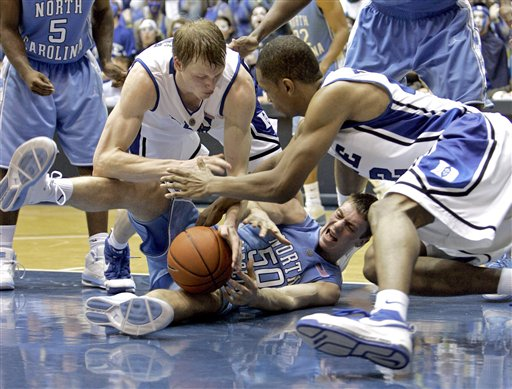 Duke's Kyle Singler (left) and  Lance Thomas battle with North Carolina's  Tyler Hansbrough for a loose  ball ...................