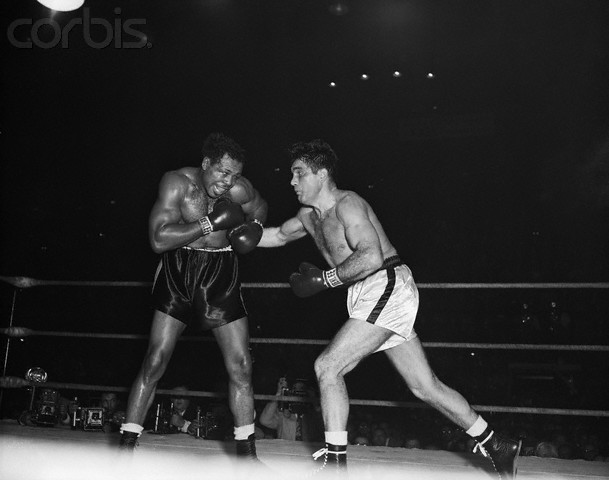 Archie   Moore  and  Joey  Maxim  face  off  for the  lightheavyweight  title .    Moore   would   go  on  to  defeat   Maxim  for  the  title .