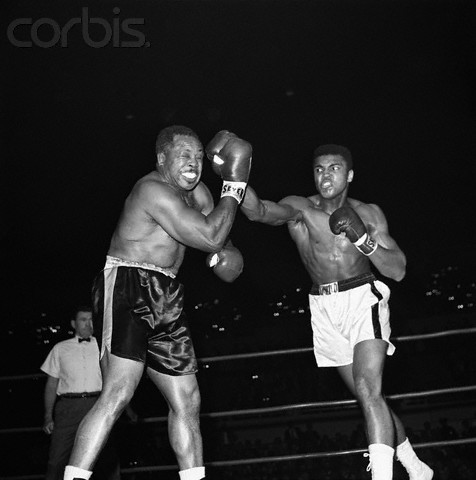 Moore  faces  off  against   a  young  Cassius  Clay  soon to  become  Muhammad Ali   in their  world  heavyweight  title  bout eliminator ................