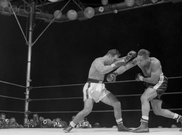 Moore  lands   a  right  to  the  midriff  of   Rocky  Marciano   in their   heavyweight title  bout.