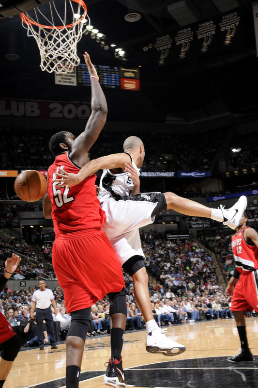 Tony Parker  of  the  Spurs  attempts  the  behind  the  back  pass  whilst being  defended  by the  Trailblazers' Greg  Oden.  The  Portland  Trailblazers  would  go  on  to defeat  the  Spurs  (95-83)   in the  game. picture appears courtesy  of nbae/getty  images/  Layne Murdoch ...............
