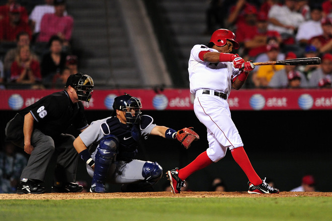 Erik Aybar  of   the  Los  Angeles   Angels   hits  the  game  winning   rbi  in a  game  played  against  the  Seattle  Mariners  at  Anaheim Stadium  ,  Anaheim  , Ca.,   The  Angels   would   defeat  the  Mariners  3-2 .     picture appears  courtesy  of  getty images/  Jacon  de  Golish  ....................