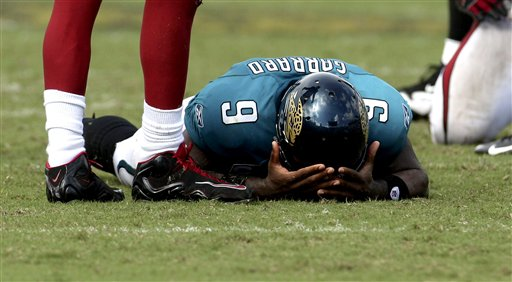 Jags'  quarterback   David  Garrard   buries his  heads  in his  hands  and  his  face  in the  turf   as   time  runs  out  in the  game   against the   Arizona  Cardinals   in a  game  played  Jacksonville  Municipal  Stadium,  Jacksonville,  Florida.    picture  appears  courtesy of   ap/photo/ Phil   Coale  ........................