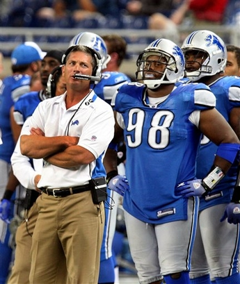 Lions' coach  Jim  Schwartz  and  the  team's  defensive tackle Lance  Cohen  (98)  look  on  from  the  sidelines as   the  waning  moments  die  down  in  an   NFL  game  played against   the Minnesota  Vikings  at  Ford  Field  in  Detroit  , Michigan.   The  Vikings  would  go  on to  defeat  the  Detroit Lions  27-13, forcing the    team  to   endure  its   19th  straight  loss  of  NFL game .  It  is  the  second  lonest mark  of  its  kind  NFL history.   picture appears  courtesy  of  ap/photo/ Carlos Osorio  ........................