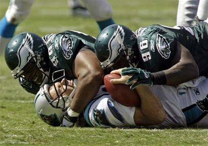 Panthers'  quarterback  Jake  Delhomme  lies  at  the  bottom  of  the  heap  having   just  been  sacked  by  the  Eagles'  defensive  players   Mike  Patterson  (98) and  Omar Gaither (96)  in  the  third   quarter  of  the  game   .    Delhomme's   performance   on the  day  ,  can  be  best  described  as  being  abysmal.     picture  appears  courtesy  of  ap/photo/   Rick   Havner  .......................