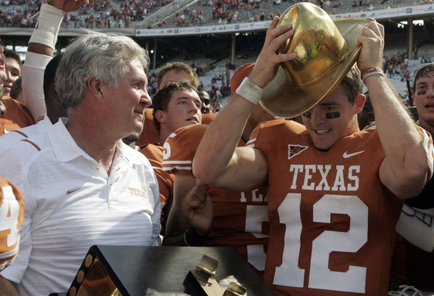 University of Texas Longhorns head coach Mack Brown (L) smiles as Longhorns quarterback Colt McCoy (R) takes the golden hat off of the Texas Oklahoma Trophy at the conclusion of their NCAA college football game against the Oklahoma University Sooners in Dallas, Texas October 17, 2009. picture appears courtesy of  Reuters / Jessica Rinaldi ......