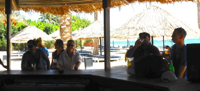 Let's just grab a drink at the beach bar while we wait for the rooms to be ready.