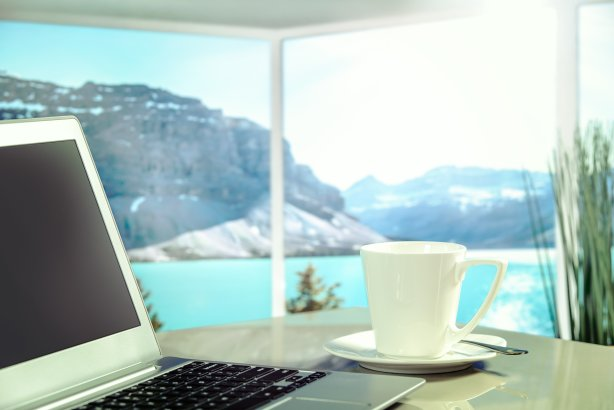 laptop and coffee cup overlooking lake