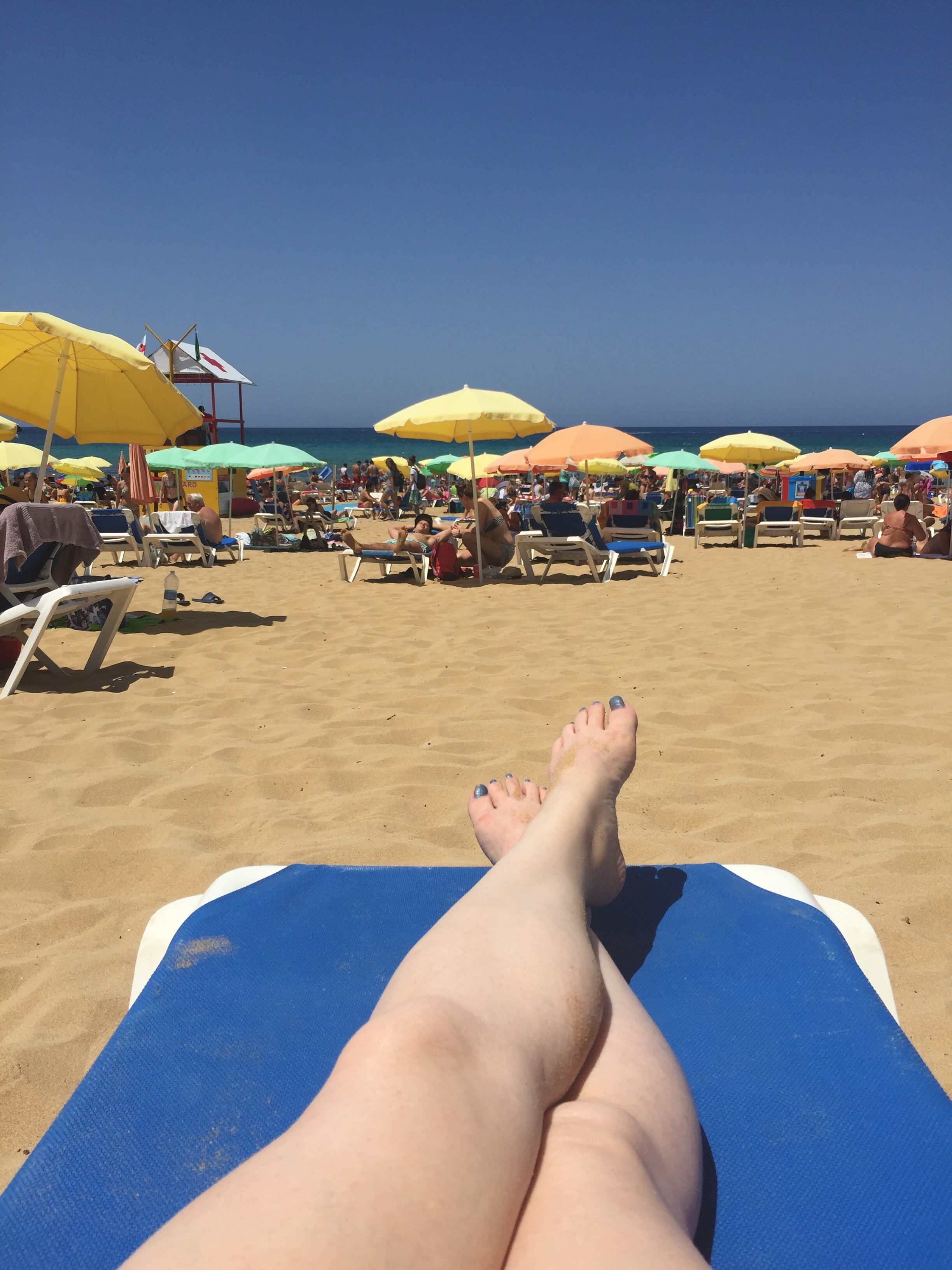 Malta beach, Golden Bay, sunbathing on lounger, bright parasols