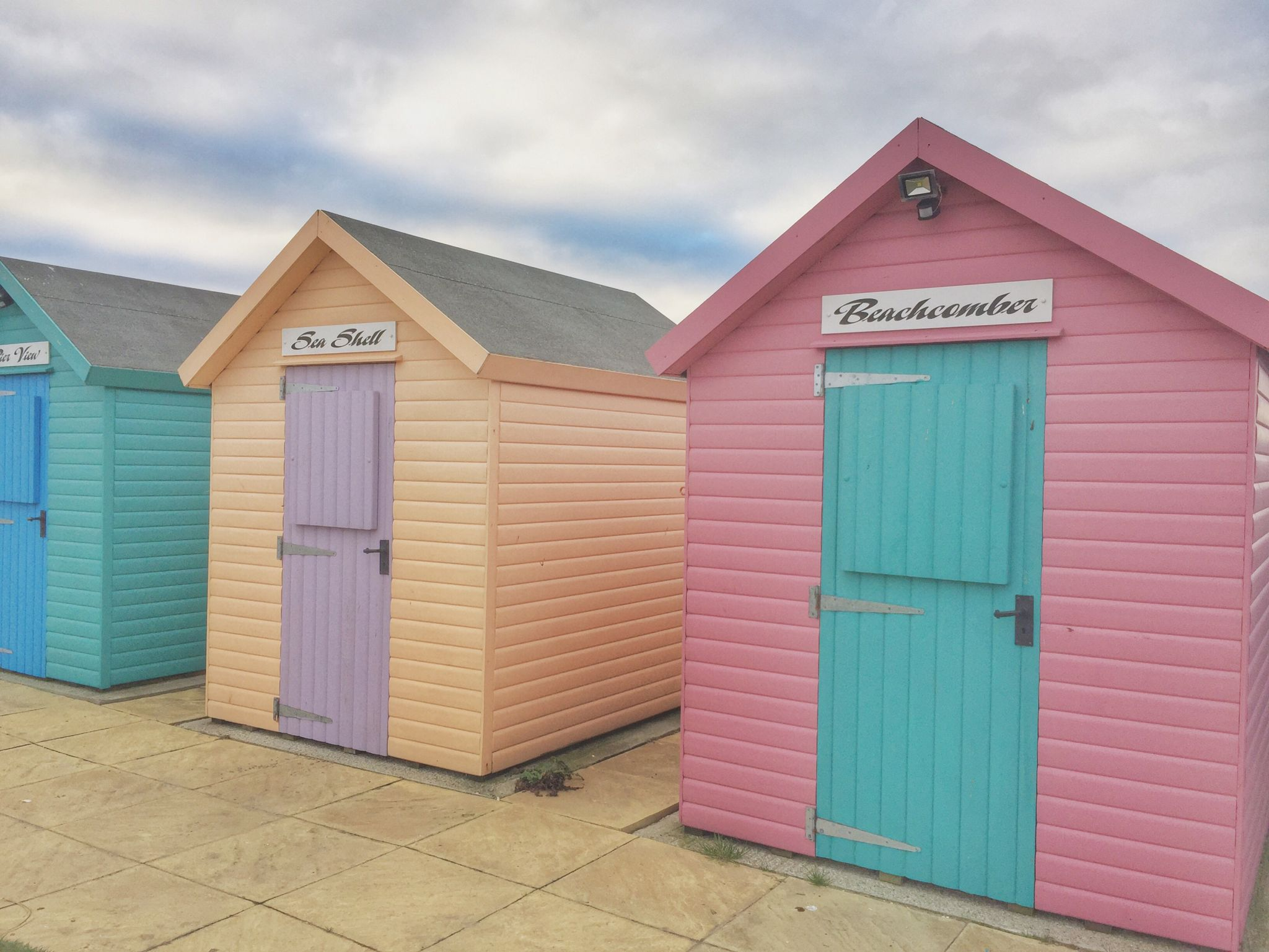 Hiking Amble to Alnmouth. Pastel colour beach huts at Amble