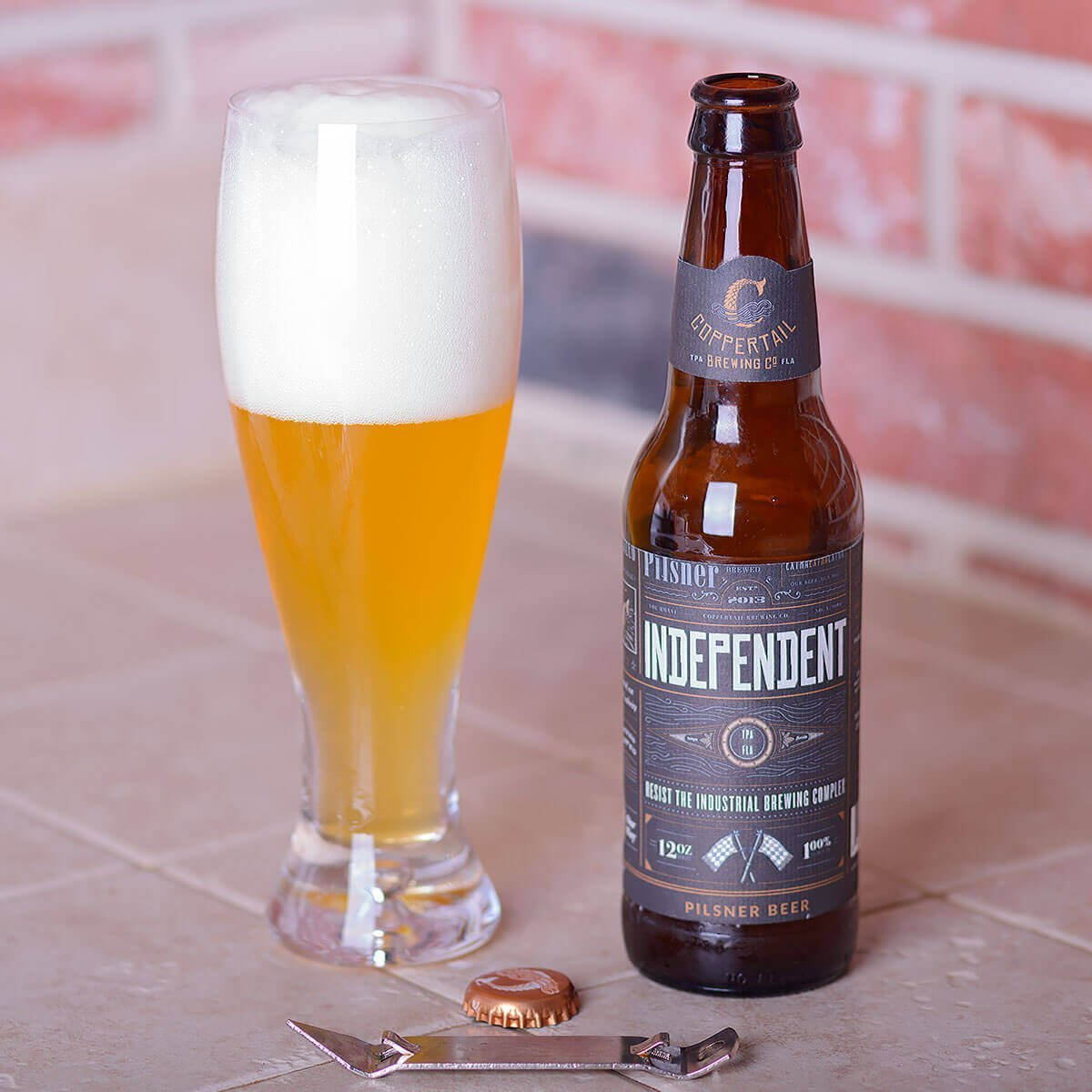 Independent Pilsner is a German-style Pilsner by Coppertail Brewing Co. that balances peppery and floral hops with cracker malt.