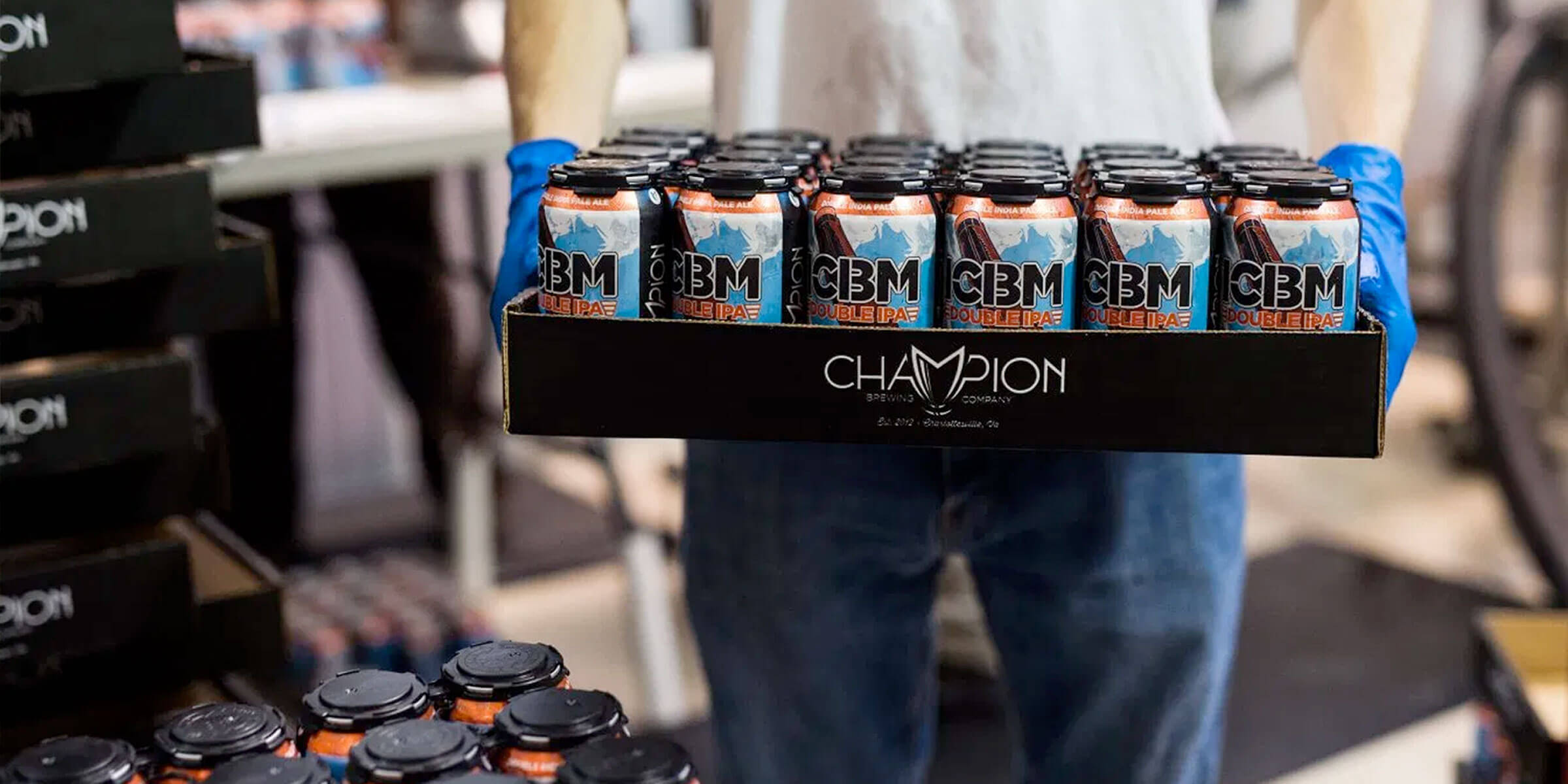 A worker stacks cases of ICBM Double IPA by Champion Brewing