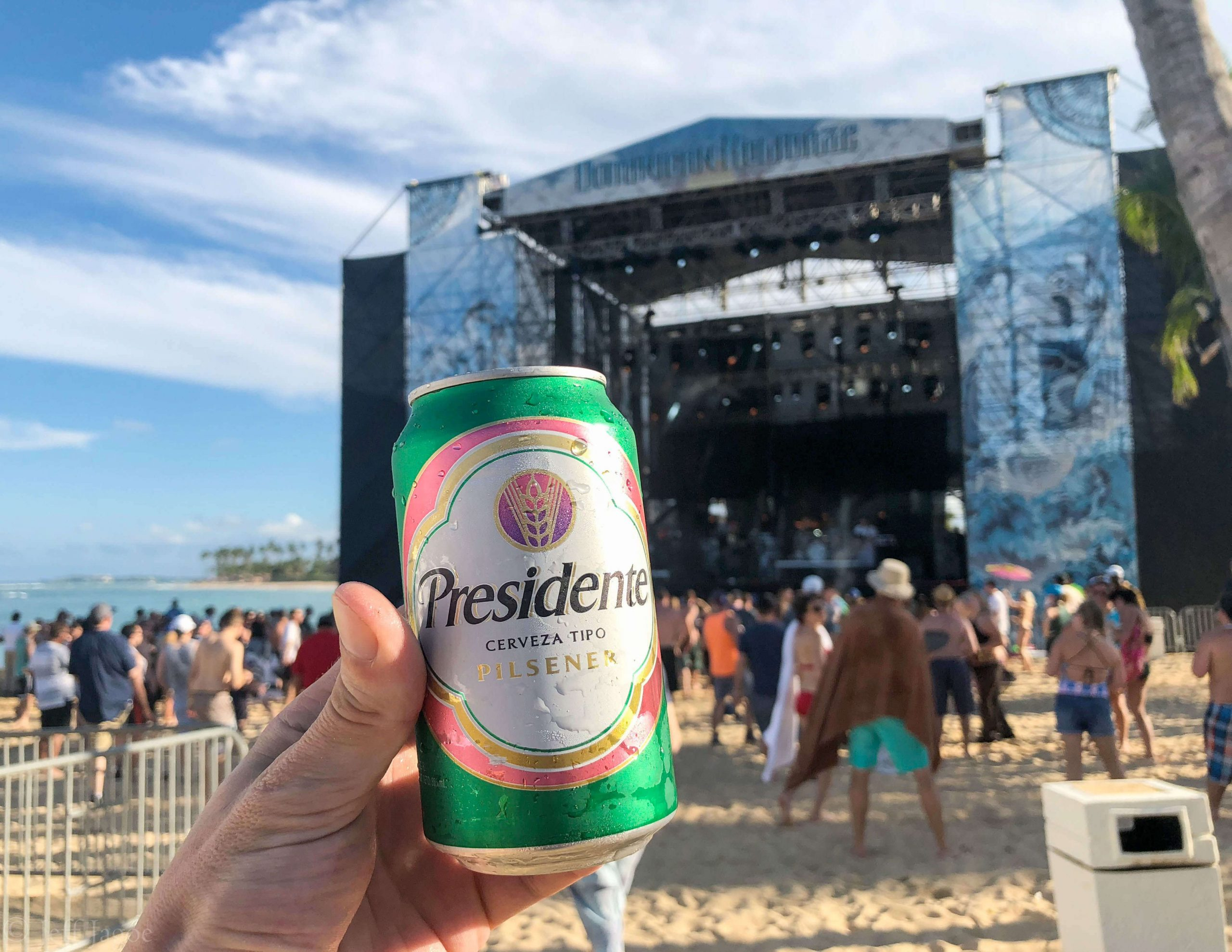 A person holds a can of 12 oz. can of Presidente beer by Cervecería Nacional Dominicana at a concert on a beach