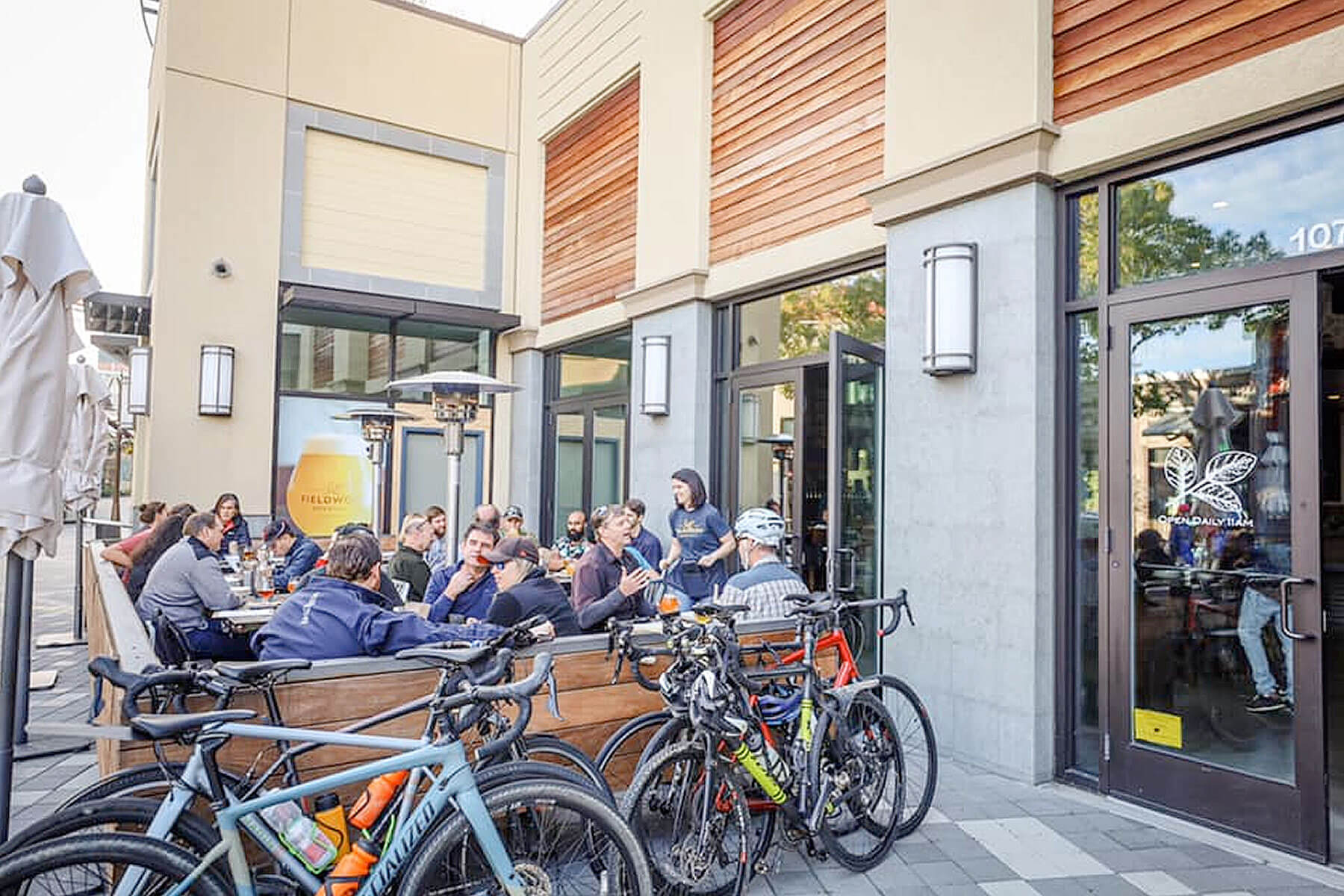 Patrons enjoy food and beer on the patio outside the taproom at Fieldwork Brewing Company in Corte Madera, California