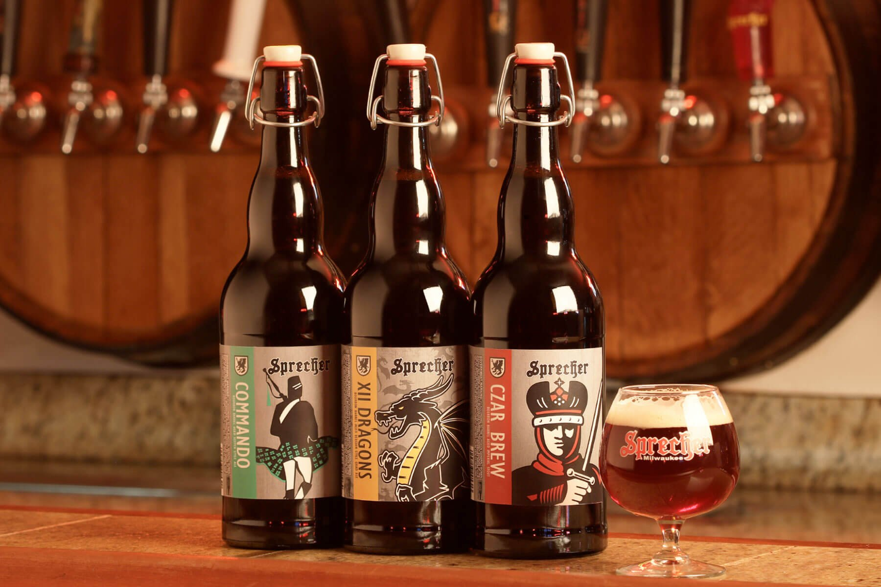 A trio of bottled beers and a branded snifter from Sprecher Brewing Company