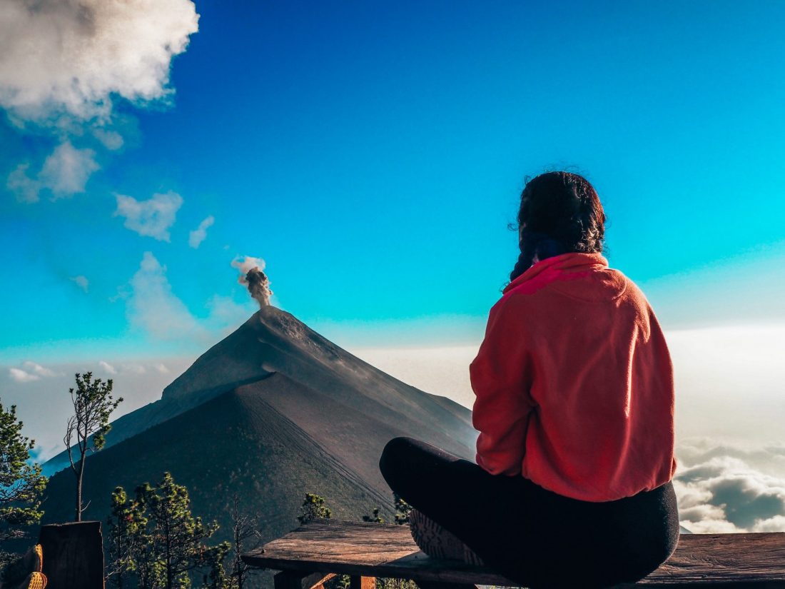 Girl in pink jumper sitting with view of Volcano Fuego from base camp on Volcano Acatenango. Near Antigua, Guatemala travel itinerary