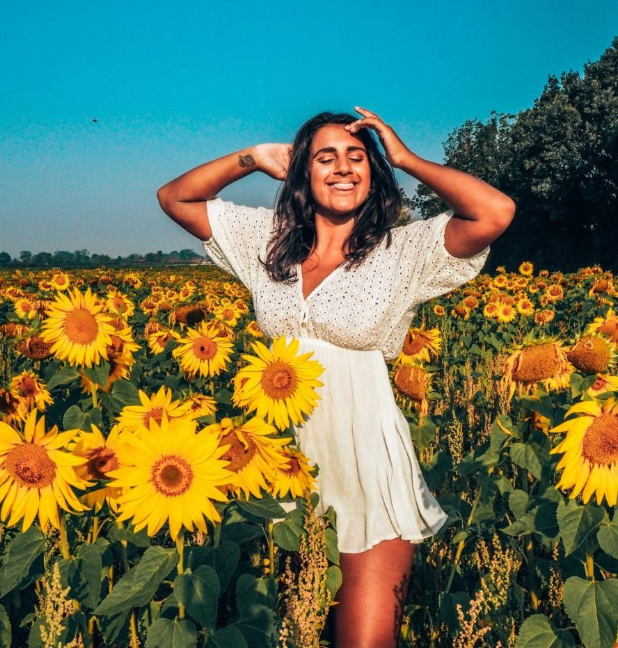 Absolutely Lucy girl in sunflower field, white dress, tattoo. TEFL certificate