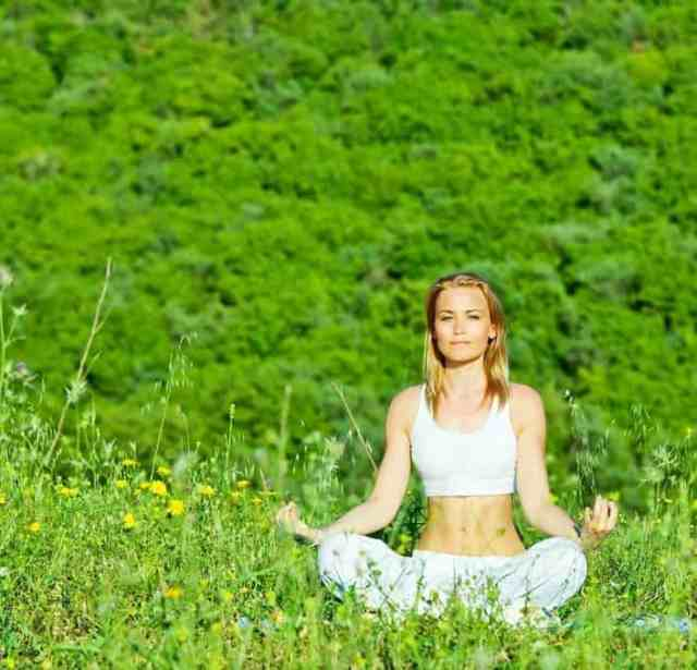 Young women meditating in field