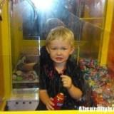 Bambino nella macchina dei peluche