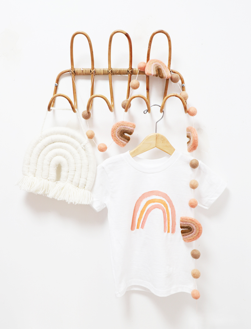 toddler boho rainbow t-shirt hanging on a rack with rainbows
