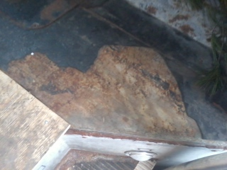 Some of the remaining old flooring, with the edge of the transmission cover plate on the upper left.