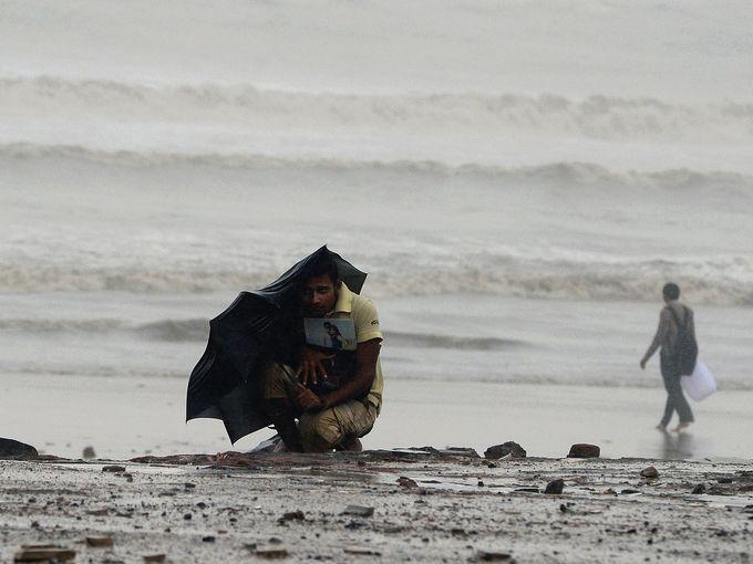 رجل يحتمي من الرياح العاتية والأمطار بمظلة