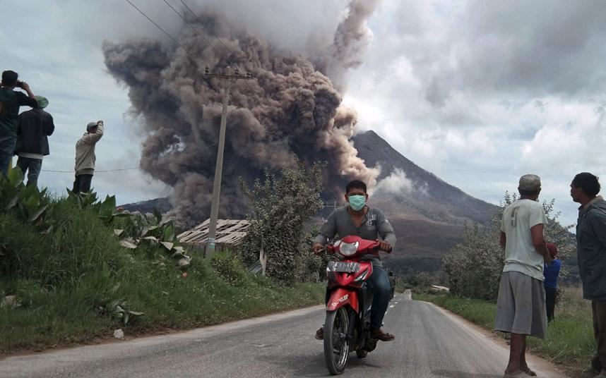 رجل يركب دراجته النارية مبتعدا عن جبل سينابونغ الذي ثار بركانه ونفث الرماد