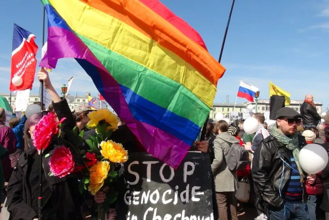 Manifestantes con una bandera arcoíris y un letrero que dice