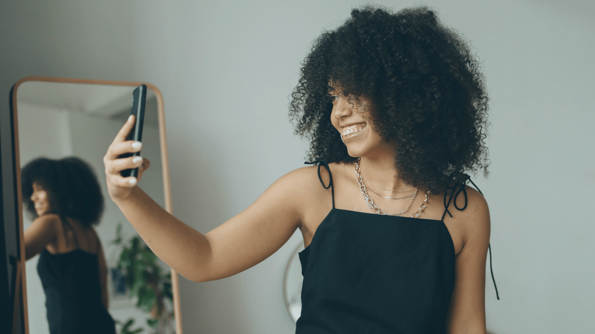 woman looking at self in phone and mirror