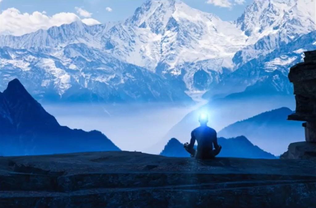 homme assis en tailleur de dos face à la montagne enneigée et devant un lac
