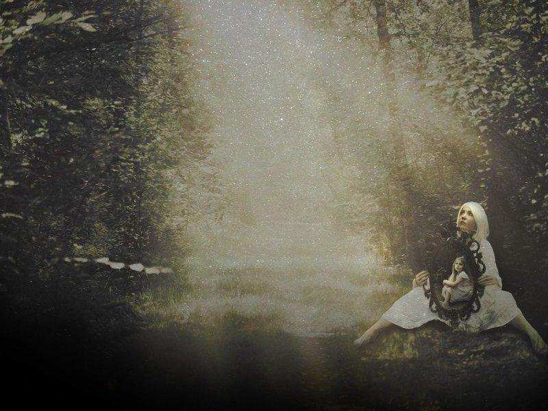 femme assise dans une forêt avec l'image de son enfant intérieur dans un miroir