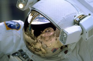The Space Shuttle's cargo bay and the Earth's horizon are reflected in the helmet visor of one of the space walking astronauts during Hubble Servicing Mission 3A.