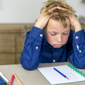 boy struggling with his homework, holding his hands in his hair
