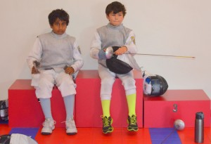 Teammates at the fencing competition wait for their next bout