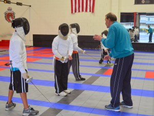 Coach Alexandr explains safety rules to new fencing students