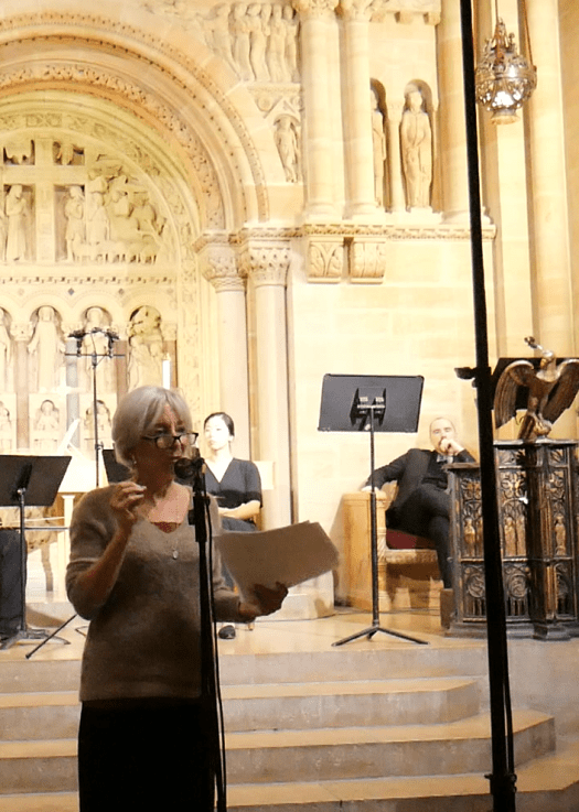 A woman speaks about Domenico Freschi's Giuditta in a microphone with a brightly lit church sanctuary in the background.