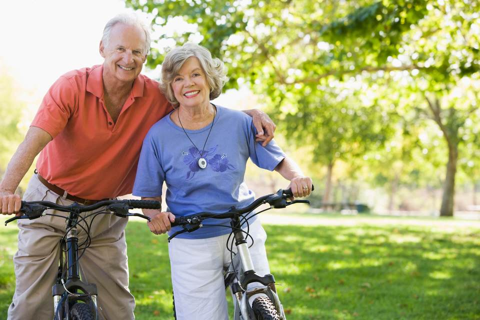 Seniors biking with mobile medical alert pendant.