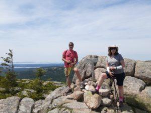 Hikers on peak of Pemetic Mountain in Acadia National Park