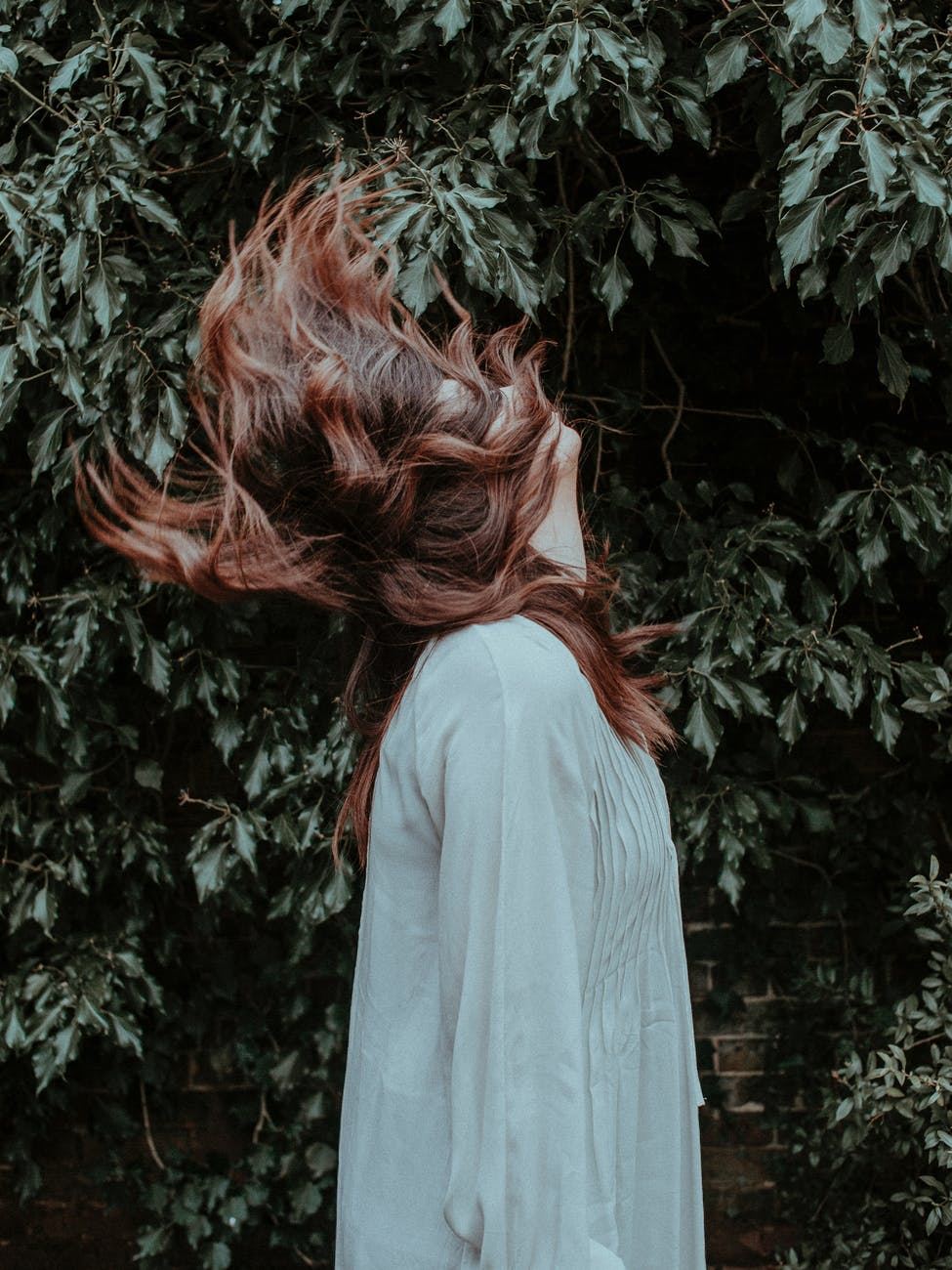 side view photo of woman in white long sleeve dress standing near green leafed plant doing hair flip